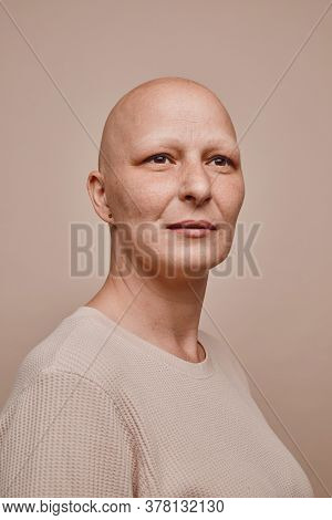 Vertical Warm-toned Portrait Of Confident Bald Woman Looking Away Hopefully While Posing Against Min