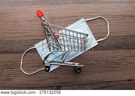 Miniature Trolley And A Facemask On A Dark Wood Background