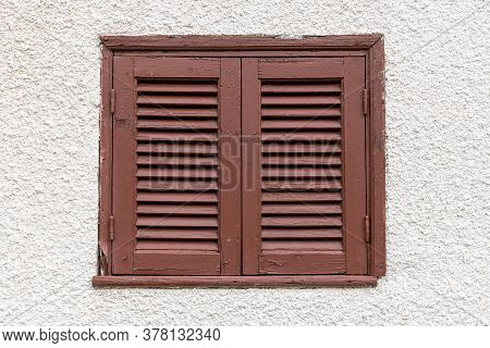 Closed Window With Brown Shutters On A Light Wall, Cyprus