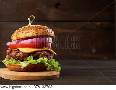 Cheeseburger With Tomatoes, Onions, Barbecue Cutlet And Sesame Bun On An Old Wooden Cutting Board, B