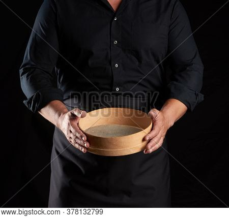 Man In Black Uniform Holding Empty Vintage Round Wooden Sieve For Sifting Flour, Chef Stands Against