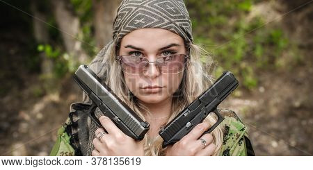 Attractive Female Soldier Posing With Two Guns. Woman With Weapon