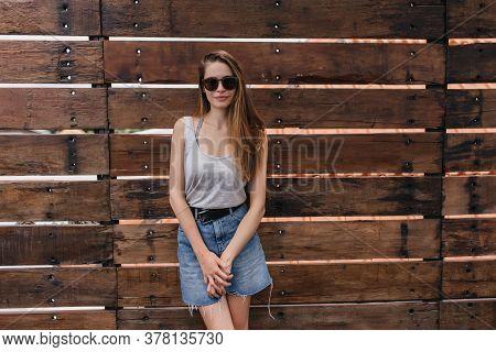Shy Girl In Trendy Denim Skirt Posing Near Wooden Wall. Outdoor Portrait Of Lovable Caucasian Lady W