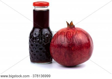 A Bottle Of Pomegranate Juice. Nearby Is A Large Beautiful Pomegranate. Studio Photo On A White Back