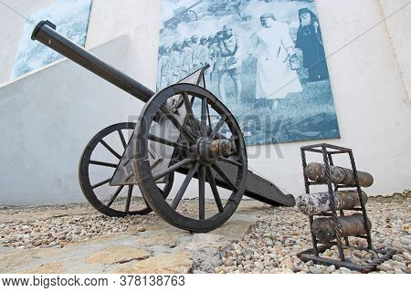 Comana, Romania On 26.07.2020. War Cannon With Ammunition And Pictures With War Theme In Background.