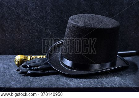 A Magician's Set Tall Hat, Leather Gloves And A Knobbed Cane On A Black Background