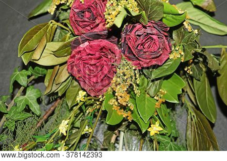 Bouquet Of Withered Red Roses And Dried Leaves
