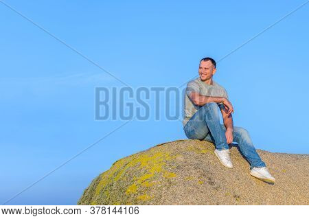 Young Athletic Attractive Man Sitting On A Rock Against A Blue Sky Background And Smiling Looking To