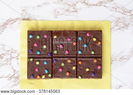 Top View Chocolate Fudge Brownies On Yellow Napkin