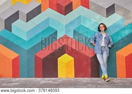 Full Body Female Hipster In Denim Clothes Leaning On Colorful Wall With Geometric Graffiti While Res