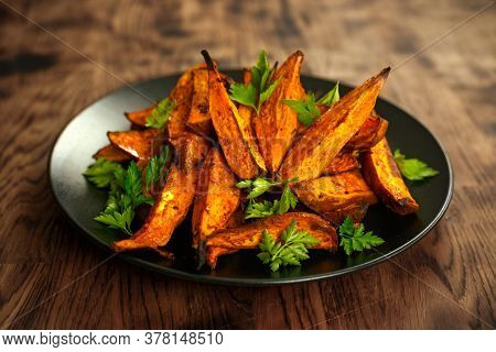 Vegetarian Oven Baked Sweet Potato Wedges, Fries Served On Black Plate With Fresh Parsley