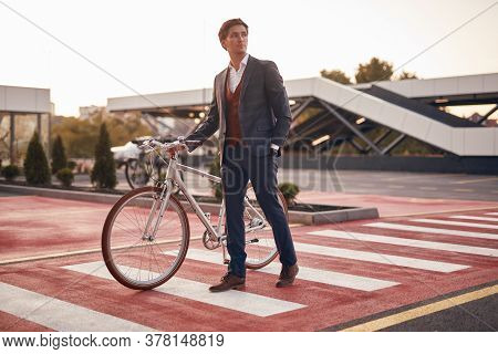 Full Body Relaxed Businessman With Hand In Pocket Looking Away And Walking With Bicycle On Crosswalk