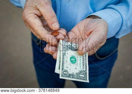 Hands Of An Elderly Man With One Us Dollar And One Cent, The Elderly Man Counts His Money. The Conce