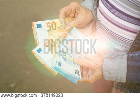 Hands Of An Elderly Woman With Euro Banknotes In Sunlight. Concept Of Prosperity, Secure Old Age, Wi