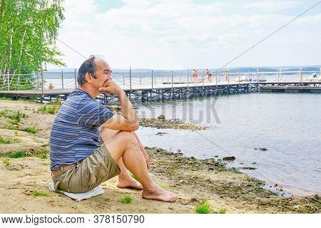 Senior Asian Man Sitting On The Sandy Beach Near The Lake And Pondering Something. Digital Detox Con