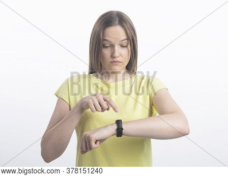Smiling Surprised Woman Using Activity Tracker Over White Background And Looking At Tracker In Surpr