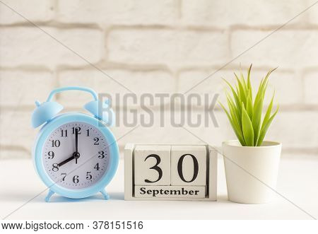September 30 On A Wooden Calendar Next To The Alarm Clock.september Day, Empty Space For Text.calend