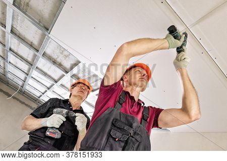 Installation Of Drywall. Workers Are Using Screws And A Screwdriver To Attach Plasterboard To The Ce