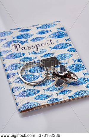 Passport With Cover And Metal Trinket For Keys In A Shape Of A Plane. Migration Or Travel Concept. I
