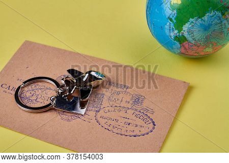 Concept Of International Mail Sending. Metal Plane Trinket On A Beige Post Envelope With Stamps. Iso