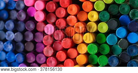 Box of crayons in a rainbow of colors background