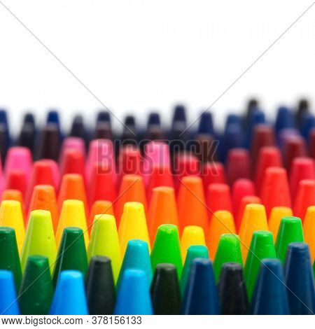 Box of crayons in a rainbow of colors with blank white space