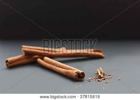 Cinnamon Sticks And Ground Cinnamon On Grey And Black Background