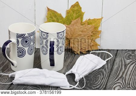Two Ceramic Mugs. Before Them Are Protective Masks For The Duration Of The Pandemic. Behind Them Are
