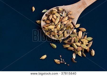 Cardamom Pods In Wooden Spoon On Deep Blue Background