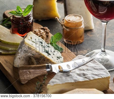 Cheese platter with organic cheeses, fruits, nuts and wine on stone background. Tasty cheese starter.