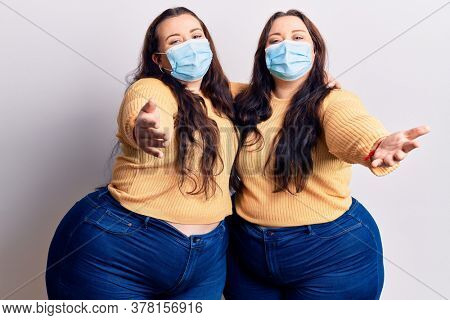 Young plus size twins wearing medical mask looking at the camera smiling with open arms for hug. cheerful expression embracing happiness.