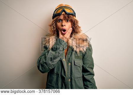 Young african american skier woman with curly hair wearing snow sportswear and ski goggles Looking fascinated with disbelief, surprise and amazed expression with hands on chin
