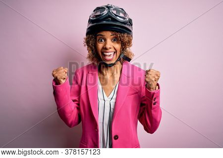 African american motorcyclist woman with curly hair wearing moto helmet over pink background celebrating surprised and amazed for success with arms raised and open eyes. Winner concept.