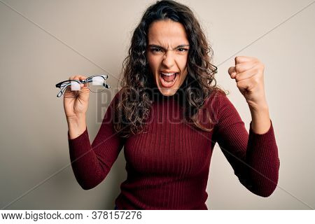 Young beautiful woman with curly hair holding glasses over isolated white background annoyed and frustrated shouting with anger, crazy and yelling with raised hand, anger concept