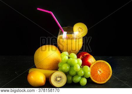 Set Of Fresh Exotic Fruits For Making Fresh Smoothies And Ready-made Smoothies In A Glass On A Black