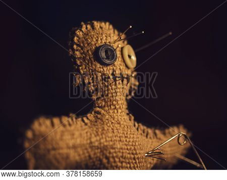 A Voodoo Doll Made Of Burlap, With Buttons For Eyes, Pierced With Many Needles Right Through The Hea