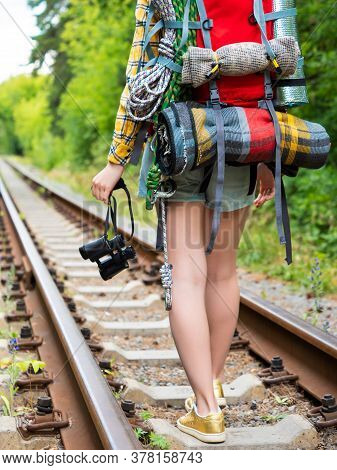 Legs Of A Woman With A Backpack Walk Along The Railway Tracks With Binoculars. Back View.