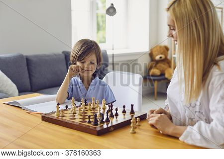 Family Hobbies. Young Mother Playing Chess With Son At Home. Little Boy Engaged In Board Game With H
