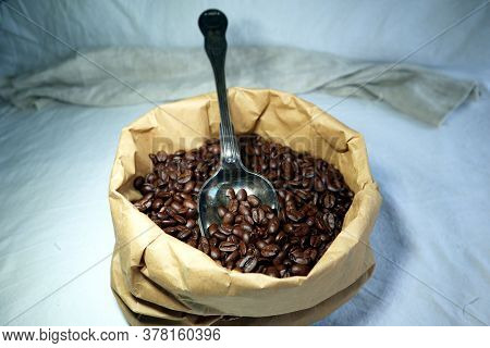 Roasted Coffeebeans In A Paper Bag With An Antique Large Spoon With Patina