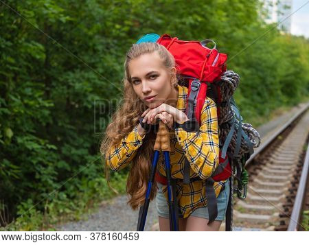 Portrait Of A Hiker Woman Ona A Railway In A Forest Looking At Camera.
