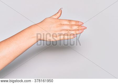 Hand of caucasian young woman stretching and reaching with open hand for handshake, showing back of the hand