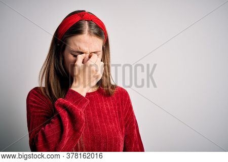 Young beautiful redhead woman wearing red casual sweater and diadem over yellow background tired rubbing nose and eyes feeling fatigue and headache. Stress and frustration concept.