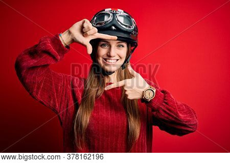 Young beautiful redhead motocyclist woman wearing moto helmet over red background smiling making frame with hands and fingers with happy face. Creativity and photography concept.