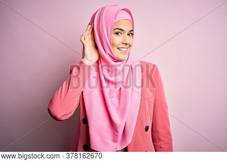 Young beautiful girl wearing muslim hijab standing over isolated pink background smiling with hand over ear listening an hearing to rumor or gossip. Deafness concept.