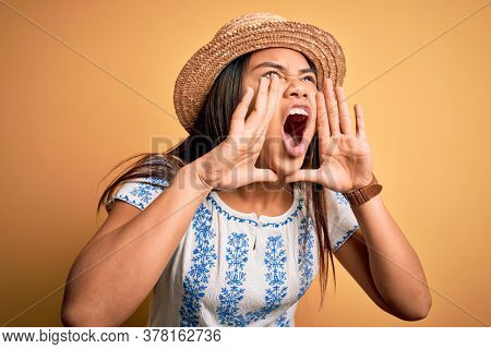 Young beautiful asian girl wearing casual t-shirt and hat standing over yellow background Shouting angry out loud with hands over mouth