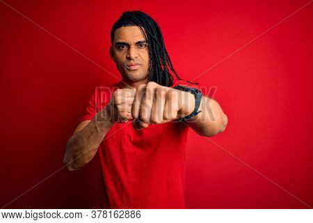 Young handsome african american afro man with dreadlocks wearing red casual t-shirt Punching fist to fight, aggressive and angry attack, threat and violence