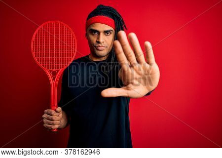African american afro sportsman with dreadlocks holding tennis racket over red background with open hand doing stop sign with serious and confident expression, defense gesture