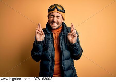 Young handsome skier man with beard wearing snow sportswear and ski goggles gesturing finger crossed smiling with hope and eyes closed. Luck and superstitious concept.