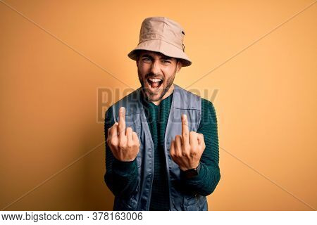 Handsome tourist man with beard on vacation wearing explorer hat over yellow background Showing middle finger doing fuck you bad expression, provocation and rude attitude. Screaming excited