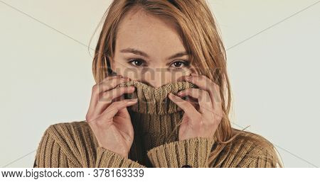Pretty happy woman wearing turtleneck against white background
